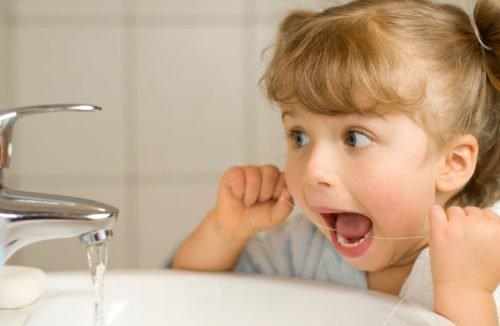 Ребенок и зубная нить для чистки